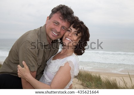Attractive and loving couple cuddling at the beach smiling