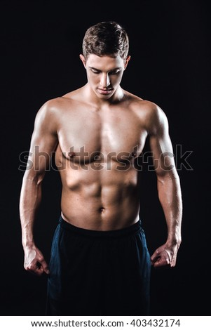 Attractive and muscular athlete. Studio shot of young shirtless sportsman on black background - stock photo
