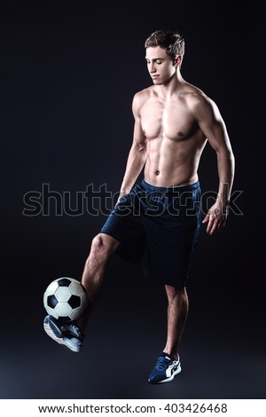 Attractive and muscular football player. Studio shot of young shirtless sportsman on black background. Man with football ball - stock photo