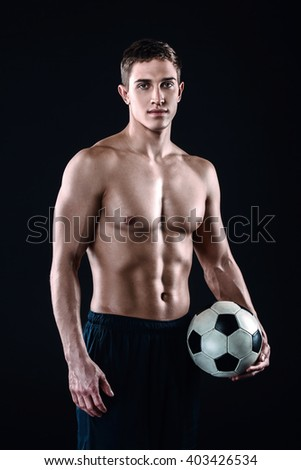 Attractive and muscular football player. Studio shot of young shirtless sportsman on black background. Man with football ball looking at camera - stock photo