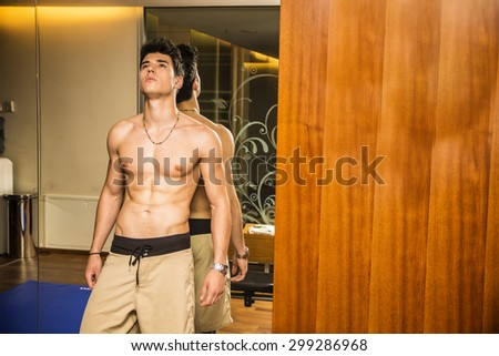 Attractive and muscular shirtless young man leaning against mirror in gym, to rest or relax after workout - stock photo