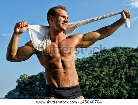 Attractive and muscular smiling bodybuilder outdoors, in nature environment - stock photo