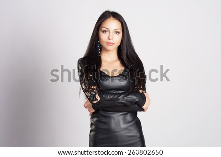 Attractive and sexy portrait of a long hair young woman in black leather dress in studio. Naked back. Fashion and glamour shot. - stock photo