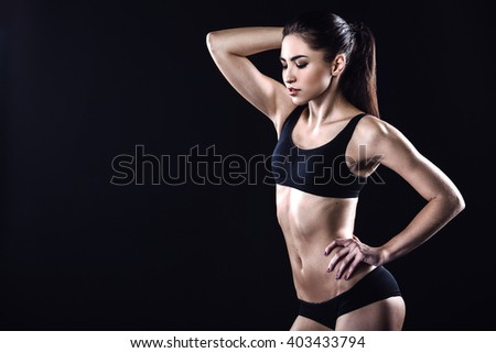 Attractive and slim woman. Studio shot of young sporty woman on black background - stock photo