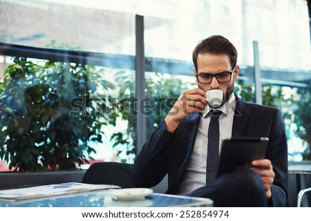 Attractive and smart business man using his tablet while having breakfast at coffee shop, businessman holding cup of coffee while read news on tablet  - stock photo