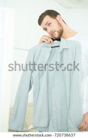 attractive and strong young man choosing shirt