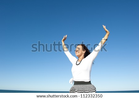 Attractive and successful looking mature woman cheerful and happy with arms up, isolated with blue sky as background and copy space.