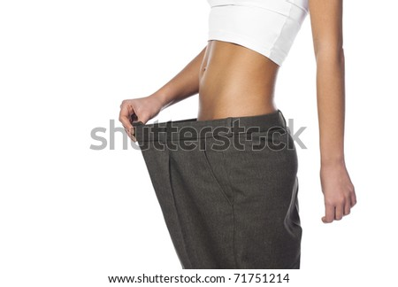 attractive and young woman showing how much weight she lost. Healthy lifestyles concept - stock photo