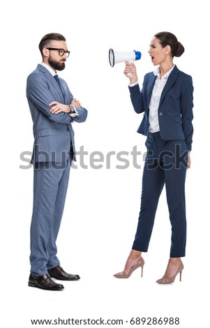 attractive angry businesswoman with megaphone screaming on her male coworker, isolated on white