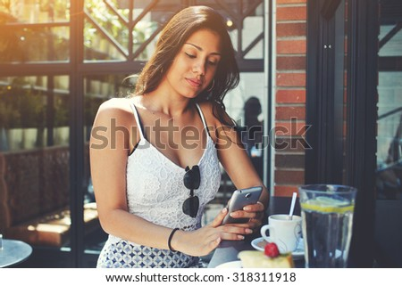 Attractive appearance confident business woman using smart phone during her work break or breakfast in cafe, young female joined the Internet via mobile phone reading some text or news in coffee shop - stock photo