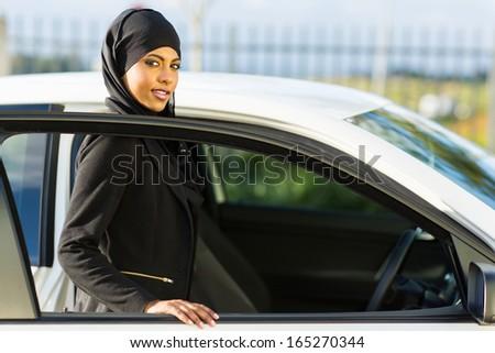 attractive arabian girl getting in a car - stock photo