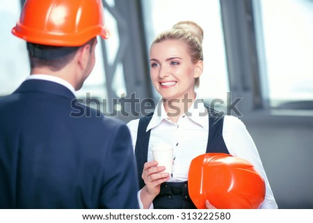 Attractive architect and his beautiful female assistant are drinking coffee on break. They are looking at each other and smiling. The workers are standing and talking about new project - stock photo