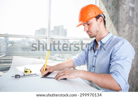 Attractive architect is drawing the sketches of new building with concentration. He is sitting at the table and holding a ruler and pencil. He is serious and confident - stock photo