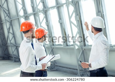 Attractive architect is explaining to the workers the plan of construction with seriousness. He is pointing his arm sideways. His colleagues are looking forward with concentration   - stock photo