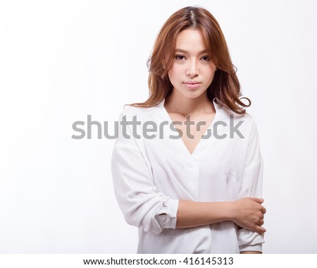 Attractive Asian American businesswoman in white blouse holding arm
