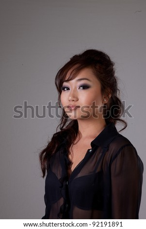 Attractive Asian American woman in black blouse and thoughtful, pensive expression