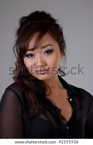 Attractive Asian American woman in black blouse and thoughtful, pouting expression