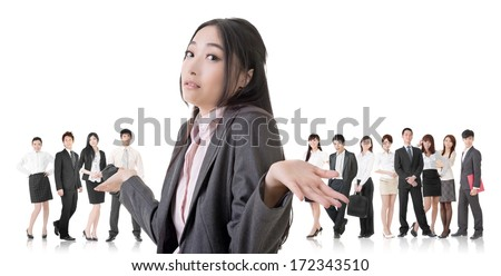 Attractive Asian business woman give you a helpless sign and stand in front of her team. - stock photo
