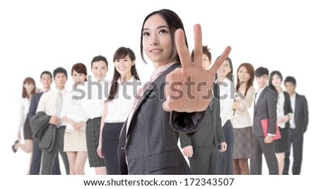 Attractive Asian business woman give you an okay sign and stand in front of her team.