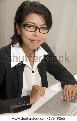Attractive Asian business woman looking at camera and smiling - stock photo