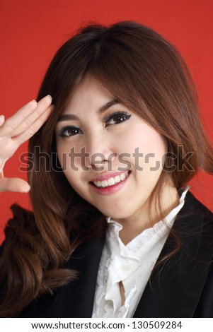 Attractive Asian business woman saluting /over red background - stock photo
