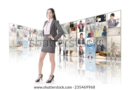 Attractive Asian business woman standing in front of TV screen wall.