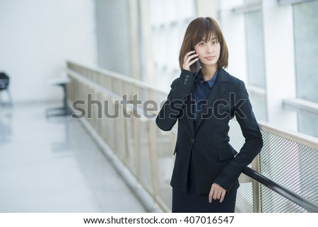 Attractive asian business woman using on smartphone outside Office