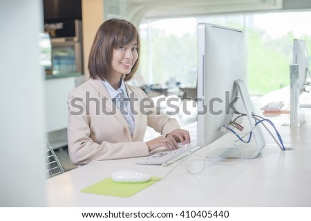 Attractive asian business woman working on computer in workplace