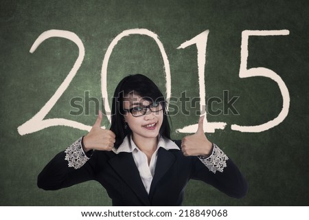 Attractive asian businesswoman showing thumbs up with a text of 2015 - stock photo