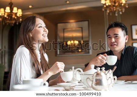 Attractive asian couple enjoying high tea - stock photo