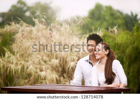 Attractive Asian Couple sitting on a table in park - stock photo