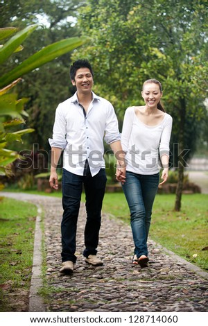 Attractive Asian Couple smiling on a date in the park