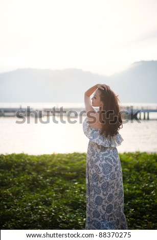 Attractive Asian Female enjoying the morning sea - stock photo