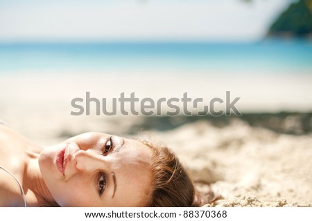 Attractive Asian Female laying on the beach with blue ocean - stock photo