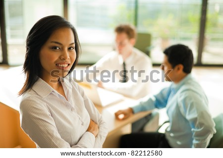 Attractive Asian female with white blouse smiling standing in foreground, looking at the camera during a business meeting, coworkers sitting at desk in background. Horizontal - stock photo
