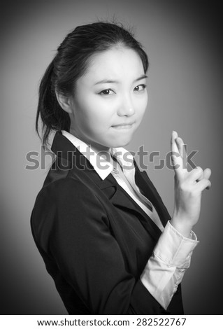 Attractive asian girl in her twenties isolated on a plain background, black and white image shot in a studio