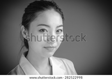 Attractive asian girl in her twenties isolated on a plain background, black and white image shot in a studio - stock photo
