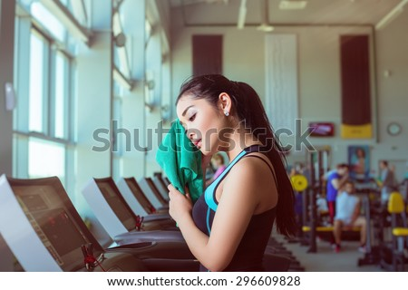 Attractive asian girl running on the treadmill in the gym with towel after training - stock photo