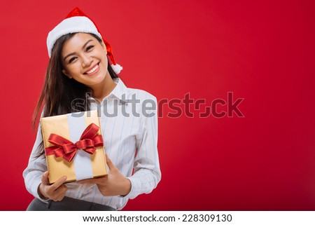 Attractive Asian girl with Christmas present in her hands, isolated on red - stock photo