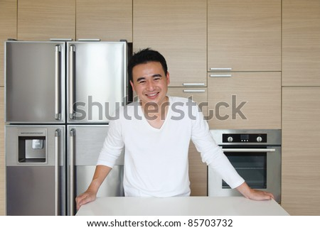 Attractive Asian Man in the kitchen smiling and happy - stock photo