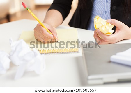 Attractive Asian woman at work in office setting with straight black hair wearing black suit and blue shirt