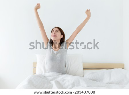 Attractive asian woman awaking on the bed