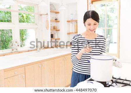 attractive asian woman cooking in the kitchen