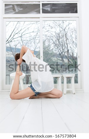 Attractive asian woman doing yoga exercise in the room