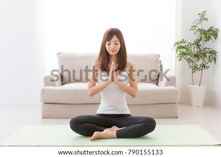attractive asian woman exercising in living room