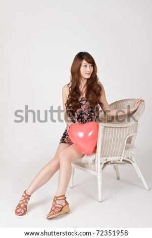 Attractive Asian woman holding balloon in heart shape and sitting on chair. - stock photo