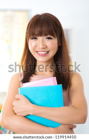 Attractive asian woman holding books at home - stock photo