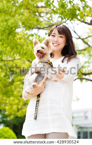 attractive asian woman holding dog in the park - stock photo