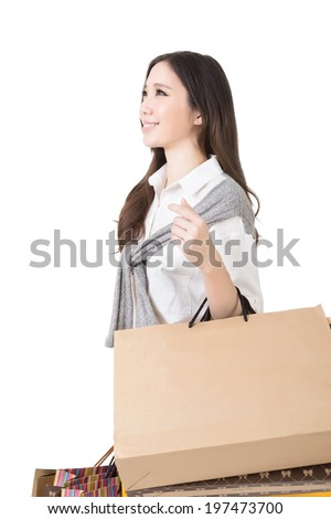 Attractive asian woman holding shopping bags and posing in studio. Side view and half length portrait. Isolated on the white background. - stock photo