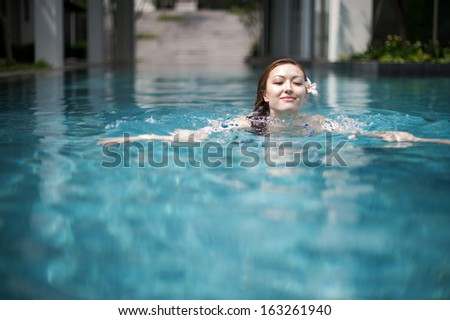 Attractive Asian Woman in Pool swimming  - stock photo